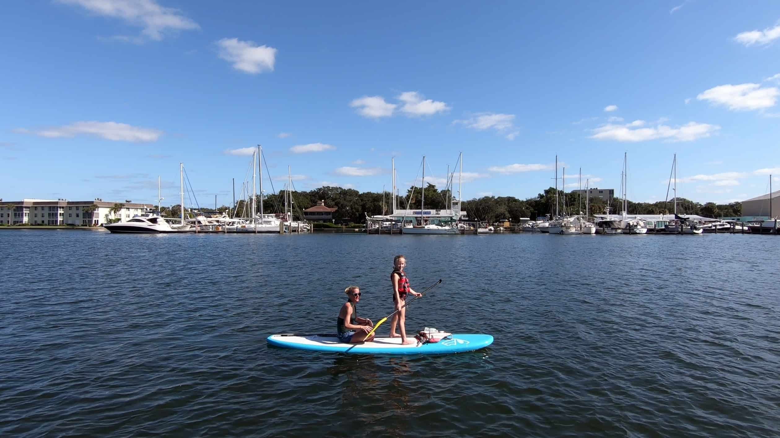 Mother sitting and daughter standing on paddle board in Vero Beach