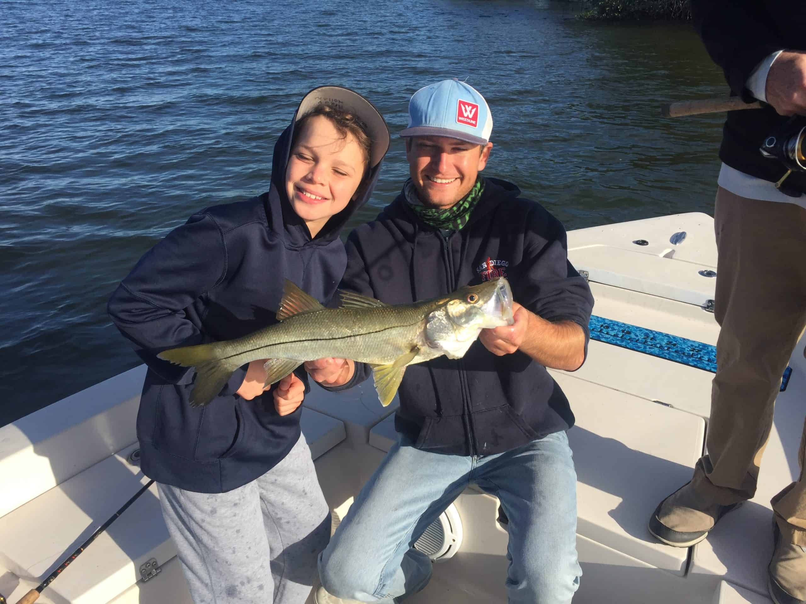 Fishing charter captain Matt Reynolds holding fish next to young boy